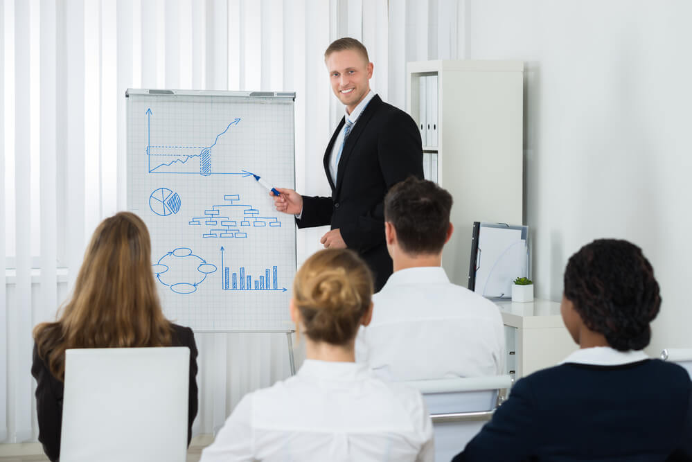 Young Businessman Explaining Business Chart On Flipchart To His Colleagues